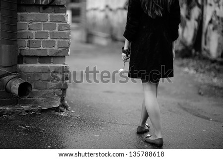 teenager dream, girls walks with a tiny tulip in hand, black and white