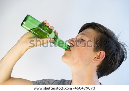 Teenager drinking beer from a green bottle. He is underage.