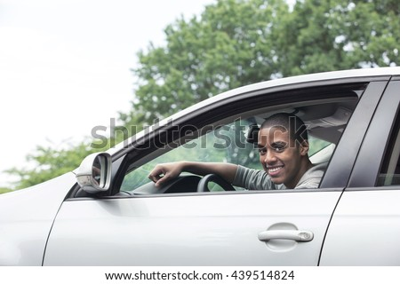 Teenager driving car - stock photo