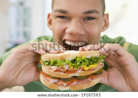 Teenager Eating A Sandwich - stock photo