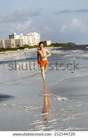 teenager enjoys jogging along the beautiful beach - stock photo
