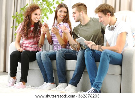 Teenager friends listening to music with different devices on a sofa