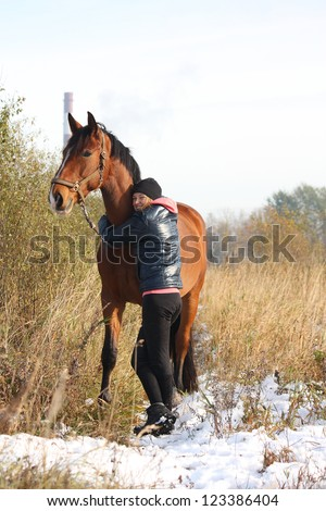 Teenager girl and bay horse standing at the crop field in winter