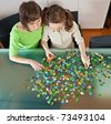 Teenager girl and her mother doing a puzzle at home - stock photo