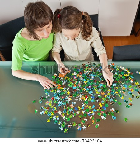 Teenager girl and her mother doing a puzzle at home