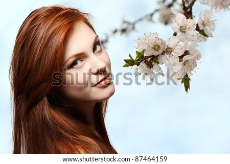 teenager girl beautiful red hair cheerful enjoying over spring flower background
