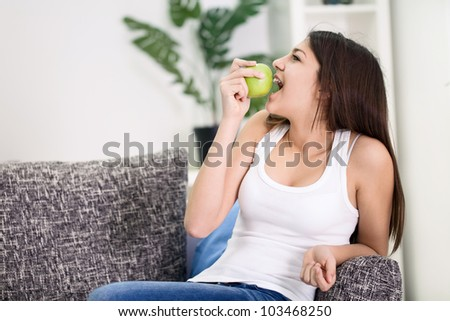 Teenager girl biting green apple - stock photo