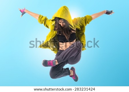 Teenager girl dancing hip hop over colorful background - stock photo