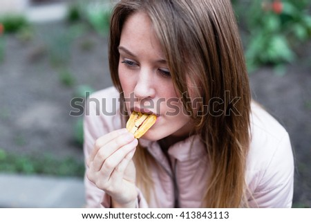 Teenager girl eating chips outdoor in street.  Beautiful young woman eating potato chips / crisps.
