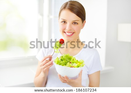 Teenager girl eating salad on light background