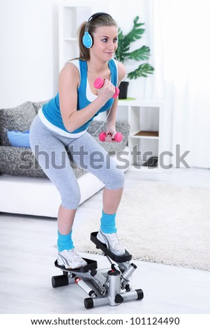 Teenager girl exercising on steeper with dumbbells