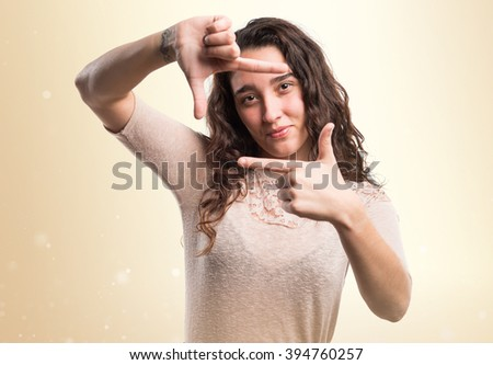 Teenager girl focusing with her fingers over ocher background