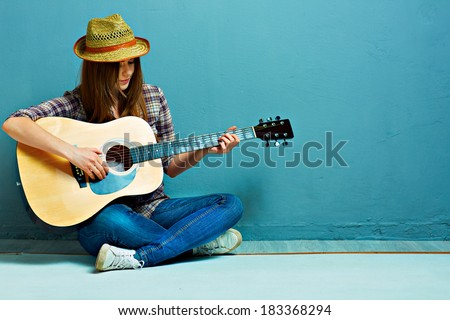 Teenager girl guitar play sitting on a floor. Blue background. Country style. - stock photo
