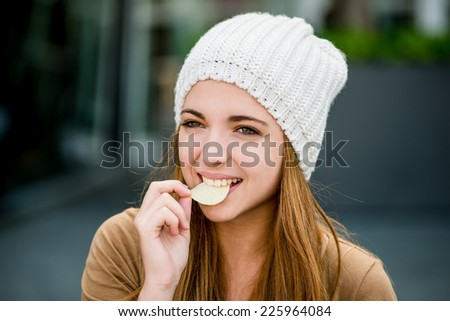 Teenager girl in cap eating chips outdoor in street - stock photo