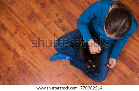 teenager girl in jeans sits on the wooden floor and holding black cat. Top view with copy space.