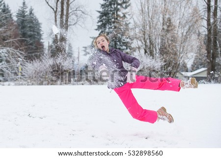 Teenager girl jumping and throwing a snowball