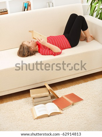 Teenager girl laying on sofa and reading books in living room - stock photo