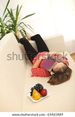 Teenager girl laying on sofa with book covering her face, listening to music - stock photo