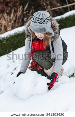 Teenager girl making snowman in snowy back yard  - stock photo