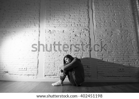 teenager girl or young woman with red hair feeling sad and scared looking overwhelmed and depressed sitting on home floor in youth depression and suffering  problem in harsh contrast light - stock photo