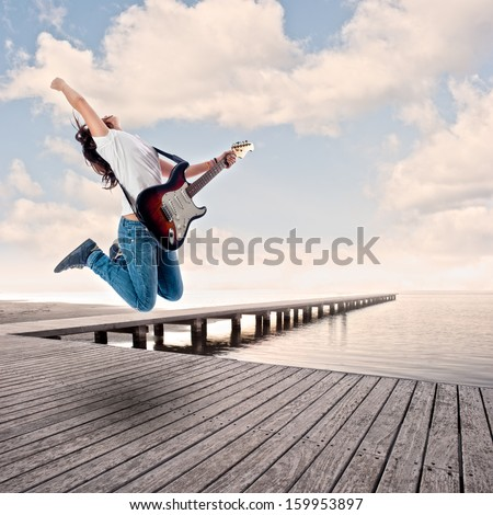 teenager girl playing electric guitar and jumping on a wharf