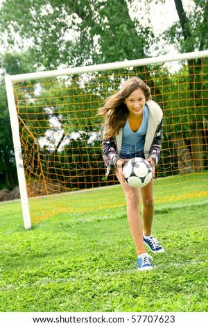 Teenager girl playing soccer and having the ball - stock photo