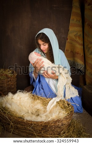 Teenager girl playing the role of the Virgin Mary with a doll in a live Christmas nativity scene (the baby is a doll).