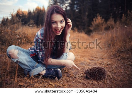 teenager girl playing with a hedgehog - stock photo