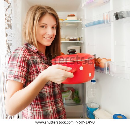 Teenager girl putting pan into refrigerator  at home - stock photo