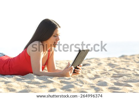 Teenager girl reading an ebook or tablet on the beach lying on the sand - stock photo
