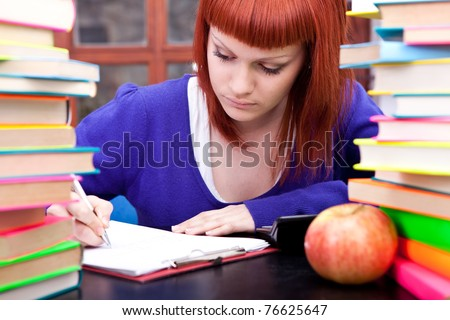 teenager girl, red hair, between piles of books writing