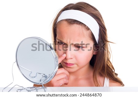 Teenager girl searching for pimples, looking in the mirror - stock photo