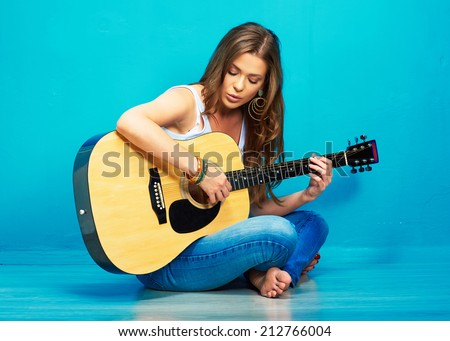 teenager girl singer with guitar sitting on a floor . - stock photo