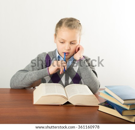 teenager girl sitting at a table in front of her large pile of books. schoolgirl reading a book and doing homework - stock photo