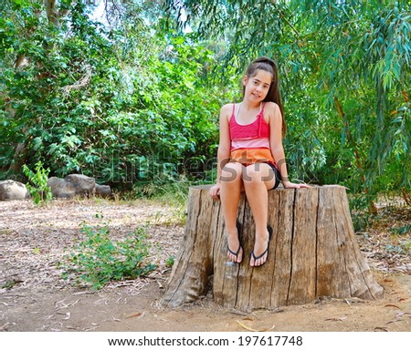 Teenager girl sitting on a sawed giant eucalyptus tree trunk in summer dress - stock photo