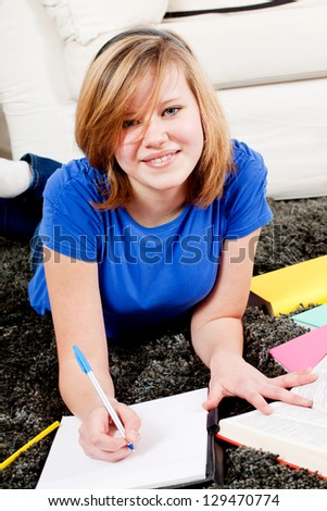 teenager girl sitting on the floor with lot of books and doing homework learning reading - stock photo