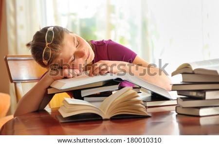 teenager girl sleeping on books, shoot in studio - stock photo