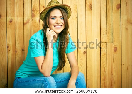Teenager girl smiling with teeth seating against wood background. Young woman portrait with hat in hipster style. - stock photo