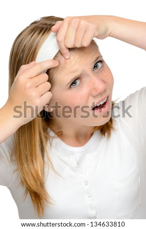 Teenager girl squeezing pimple skin problems spot cleaning face