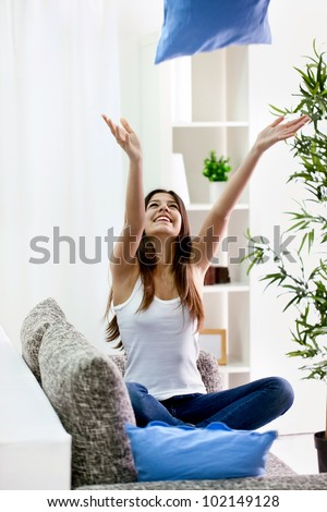 Teenager girl throwing  pillow into the air, having fun - stock photo