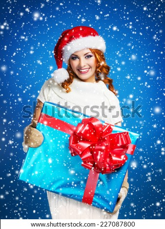 Teenager girl with a big Christmas present over winter background with a snowflakes - stock photo