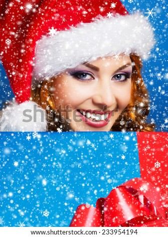 Teenager girl with a big Christmas present over winter background with a snowflakes