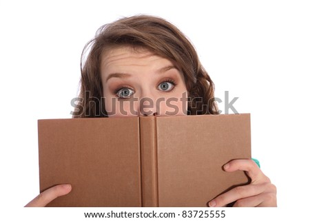 Teenager girl with big blue eyes wide open in surprise from reading a book.