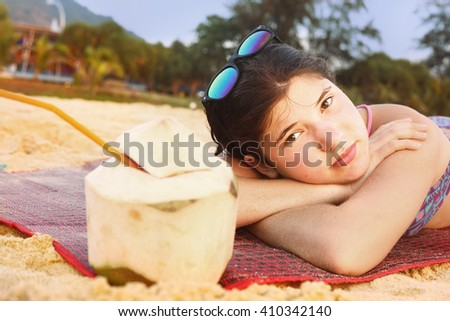 teenager girl with coconut and straw lay on the beach close up portrait - stock photo
