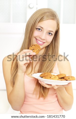 Teenager girl with cookies on a light background