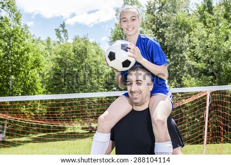 teenager girl with father play soccer