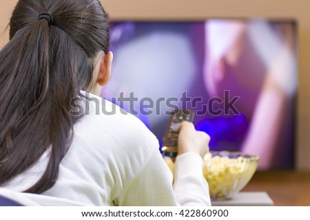 Teenager girl with remote control laying down and watching smart tv and eating popcorn.