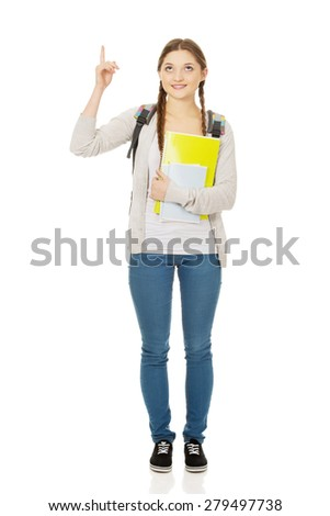 Teenager girl with school backpack pointing up. - stock photo