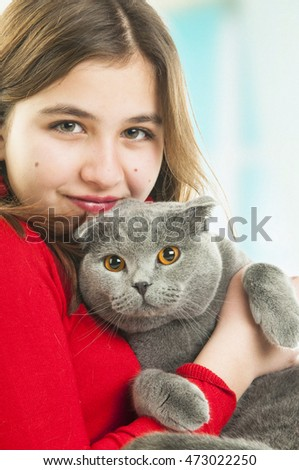 Teenager girl with Scottish Fold gray cat