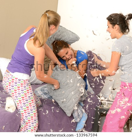 Teenager girls pillow fighting in bedroom with flying feathers - stock photo